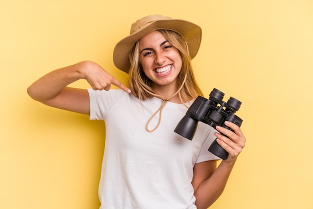 Junge kaukasische frau mit fernglas isoliert auf gelbem hintergrund person, die mit der hand auf einen hemdkopierraum zeigt, stolz und selbstbewusst