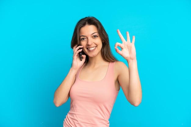 Junge kaukasische frau mit handy auf blauem hintergrund isoliert, die ein ok-zeichen mit den fingern zeigt