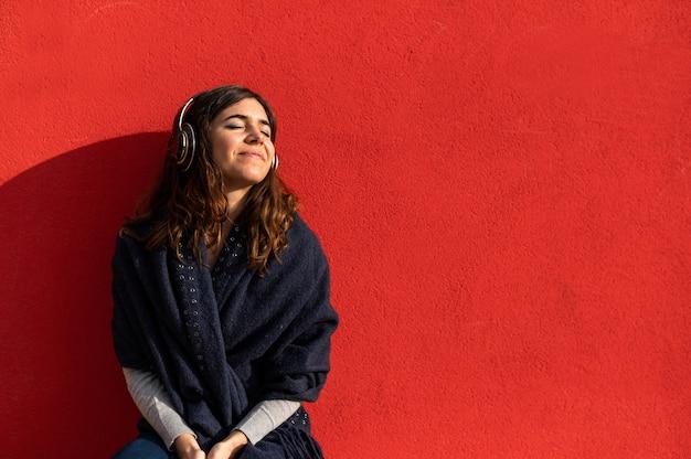 Junge kaukasische frau mit kopfhörern hört musik mit positivem smiley-gesicht. auf rotem hintergrund isoliert.