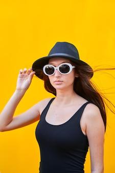 Junge kaukasische frau mit langhaariger sonnenbrille, schwarzem hut, trägershirt und schwarzer hose, hand auf hut