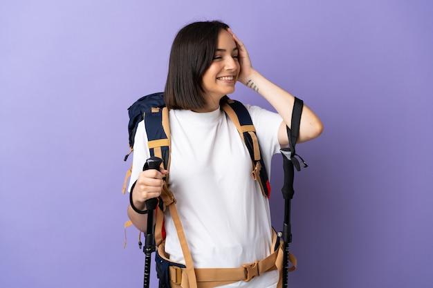 Junge kaukasische frau mit rucksack und wanderstöcken lokalisiert auf blau, das viel lächelt