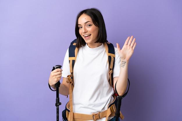 Junge kaukasische frau mit rucksack und wanderstöcken lokalisiert auf blauer wand, die mit hand mit glücklichem ausdruck salutiert