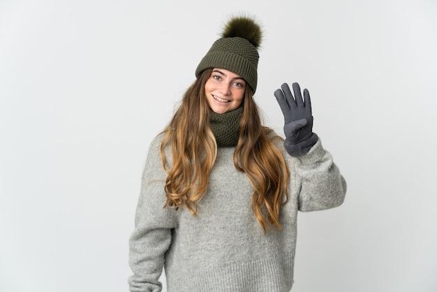 Junge kaukasische frau mit wintermütze auf weiß glücklich und zählt vier mit den fingern