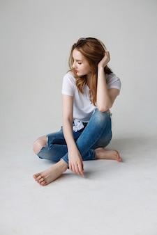 Junge kaukasische frau posiert in t-shirt, zerrissenen jeans, sitzt auf studioboden