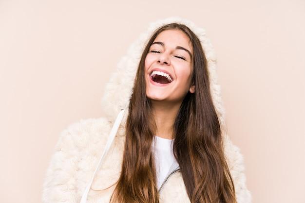 Junge kaukasische frau posiert isoliert entspannt und glücklich lachend, hals gestreckt zeigt zähne.