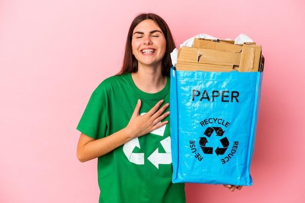 Junge kaukasische frau recycelte pappe, die auf rosafarbenem hintergrund isoliert ist, lacht laut und hält die hand auf der brust.