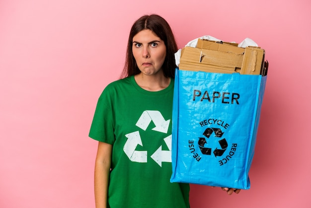 Junge kaukasische frau recycelte pappe, die auf rosafarbenem hintergrund isoliert ist, zuckt die schultern und öffnet die augen verwirrt.