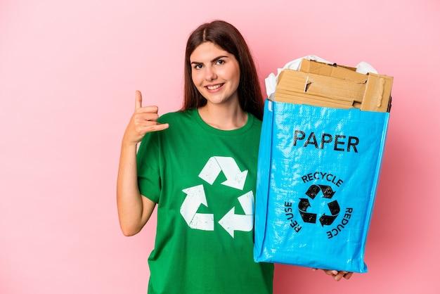 Junge kaukasische frau recycelte pappe einzeln auf rosafarbenem hintergrund, die eine handy-geste mit den fingern zeigt.
