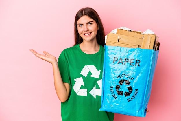 Junge kaukasische frau recycelte pappe einzeln auf rosafarbenem hintergrund, die einen kopienraum auf einer handfläche zeigt und eine andere hand an der taille hält.