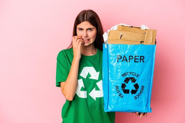 Junge kaukasische frau recycelte pappe einzeln auf rosafarbenem hintergrund, die fingernägel beißt, nervös und sehr ängstlich.