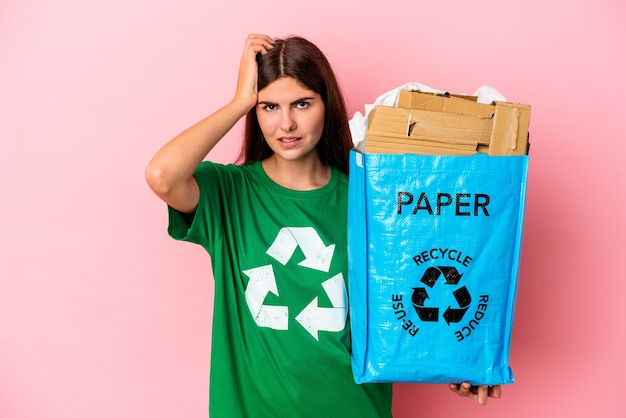 Junge kaukasische frau recycelte pappe einzeln auf rosafarbenem hintergrund und ist schockiert, sie hat sich an ein wichtiges treffen erinnert.