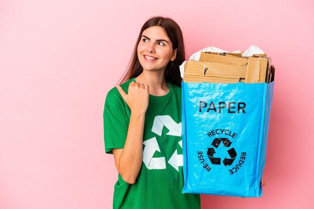 Junge kaukasische frau recycelte pappe einzeln auf rosafarbenem hintergrund, zeigt mit dem daumen weg, lacht und sorglos.