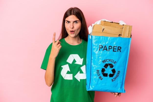 Junge kaukasische frau recycelte pappe lokalisiert auf rosa hintergrund, die einige große idee, konzept der kreativität hat.