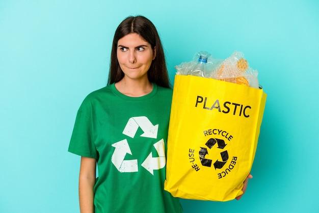 Junge kaukasische frau recycelte plastik isoliert auf blauem hintergrund verwirrt, fühlt sich zweifelhaft und unsicher.