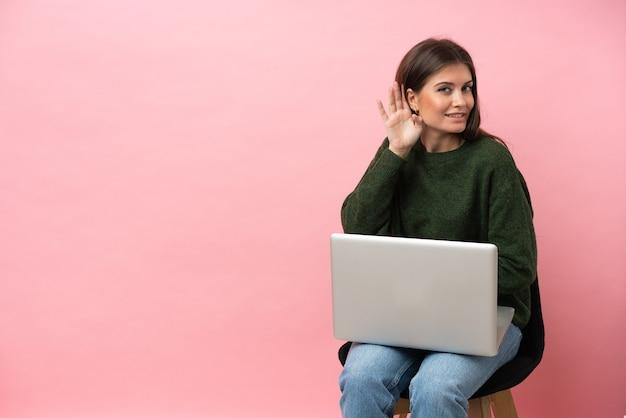 Junge kaukasische frau sitzt auf einem stuhl mit ihrem laptop isoliert auf rosa hintergrund und hört etwas, indem sie die hand auf das ohr legt
