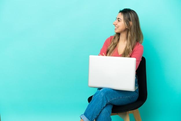Junge kaukasische frau sitzt auf einem stuhl mit ihrem pc isoliert auf blauem hintergrund mit verschränkten armen und glücklich arms