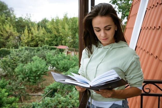 Junge kaukasische frau steht auf dem balkon mit einem notizbuch in der hand liest aufzeichnungen