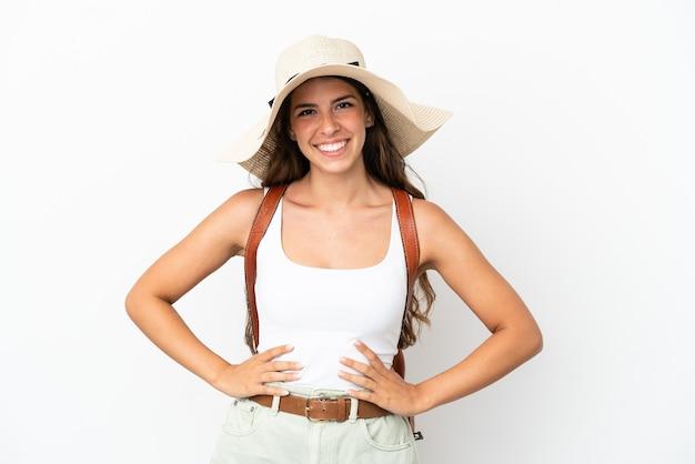 Junge kaukasische frau trägt eine pamela in den sommerferien isoliert auf weißem hintergrund posiert mit armen an der hüfte und lächelt