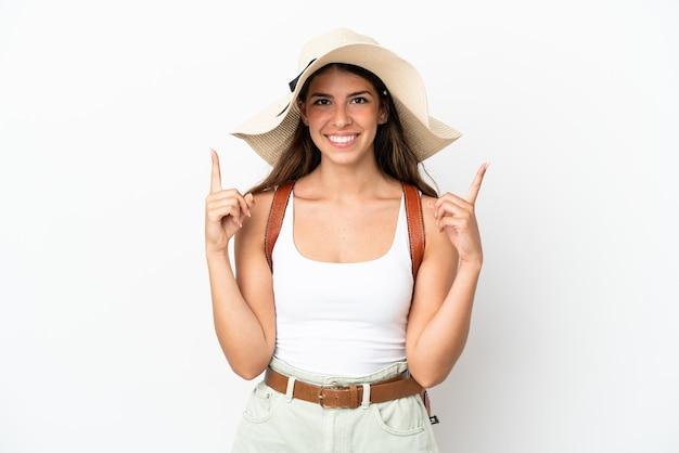 Junge kaukasische frau trägt eine pamela in den sommerferien isoliert auf weißem hintergrund und zeigt eine großartige idee