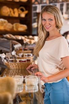 Junge kaukasische frau vor bäckerei-lebensmittelgeschäftfenster