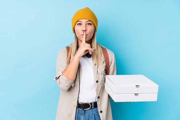 Junge kaukasische frau, welche die pizzas lokalisiert hält, ein geheimnis halten oder um ruhe bittet.