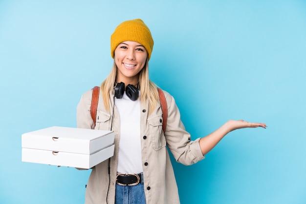 Junge kaukasische frau, welche die pizzas lokalisiert zeigen einen kopienraum auf einer palme hält und eine andere hand auf taille hält.