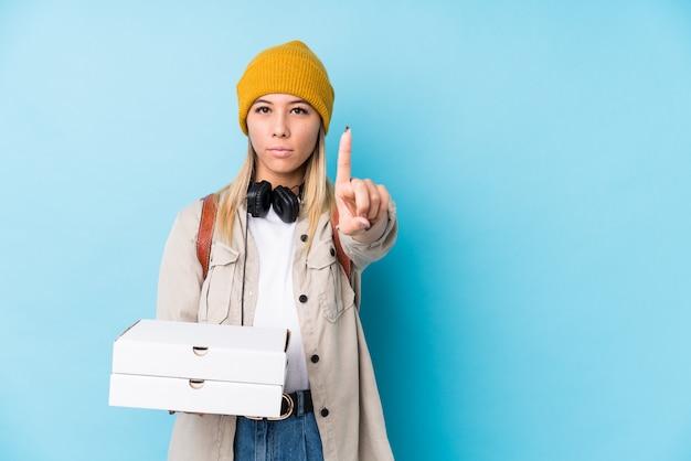 Junge kaukasische frau, welche die pizzas lokalisiert zeigen nummer eins mit dem finger hält.