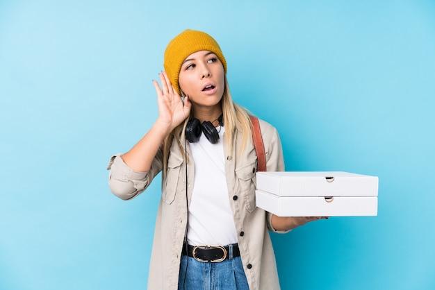 Junge kaukasische frau, welche die pizzas versuchen, einen klatsch zu hören hält.