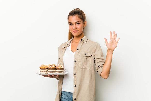 Junge kaukasische frau, welche die süßen kuchen lächeln nette darstellende nr. fünf mit den fingern hält.