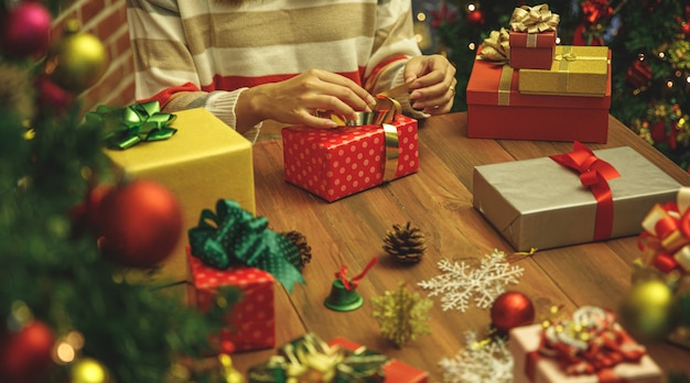 Junge kaukasische frau zieht einen wunderschönen bogen auf der geschenkbox auf dem schreibtisch als handwerk, das daran arbeitet, ein luxuriöses geschenk und eine schöne verzierung für die weihnachtsfeierdekoration vorzubereiten, um den winterurlaub im dezember zu feiern