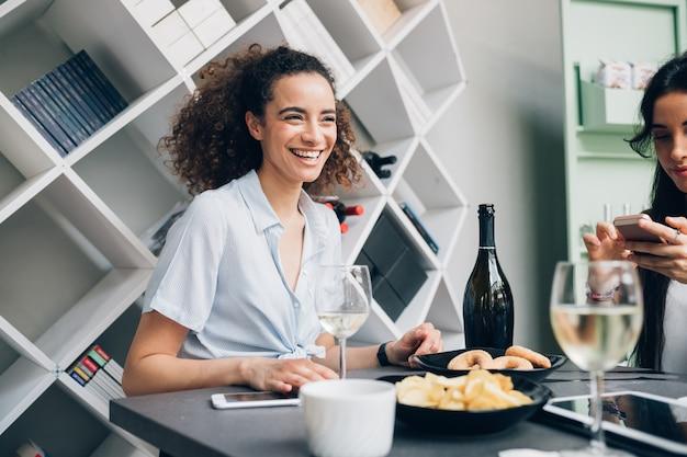 Junge kaukasische frauen, die wein trinken und im modernen restaurant sich entspannen