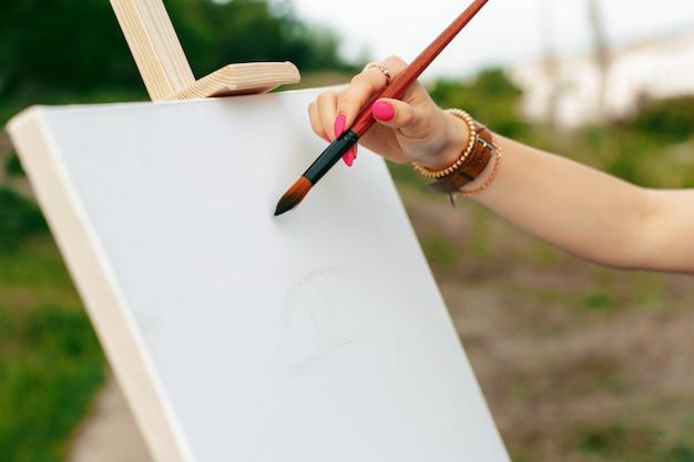 Junge kaukasische frauenmalerei auf segeltuch draußen