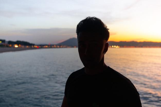 Junge kaukasische frauensilhouette mit dem meer dahinter