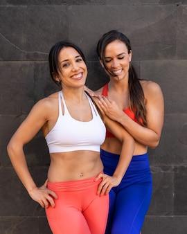 Junge kaukasische freundinnen, die übungen machen und sich außerhalb dehnen - gesundes lebensstilkonzept