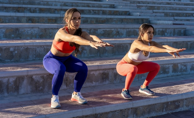 Junge kaukasische freundinnen, die übungen machen und sich draußen dehnen - gesundes lebensstilkonzept