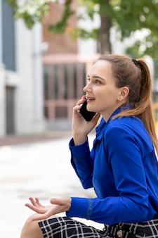 Junge kaukasische führungskraft, die freudig am telefon spricht, während sie sich auf der straße ausruht