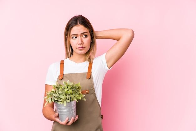 Junge kaukasische gärtnerfrau auf rosa, die hinterkopf berührt, denkt und eine wahl trifft.