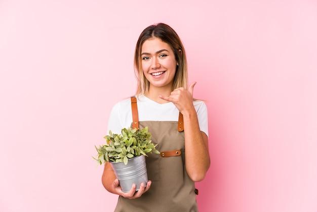 Junge kaukasische gärtnerfrau in einer rosa oberfläche, die eine handy-anrufgeste mit den fingern zeigt.