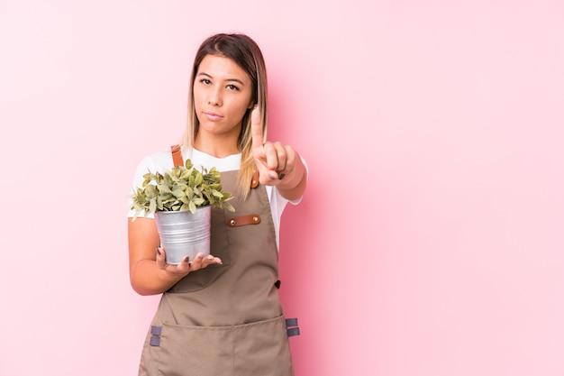 Junge kaukasische gärtnerin, die nummer eins mit finger zeigt.