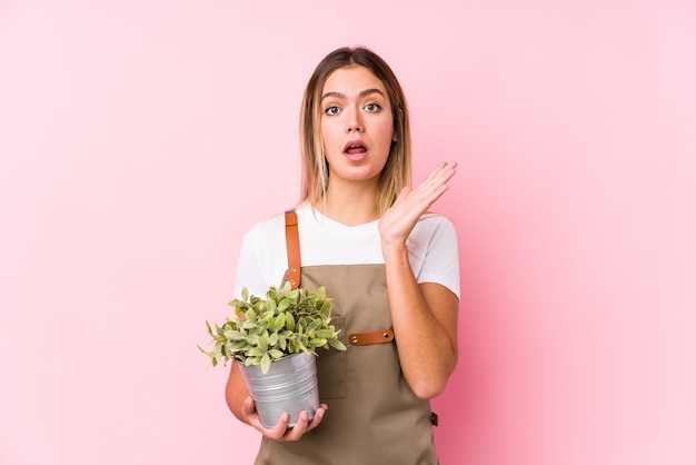 Junge kaukasische gärtnerin in einem rosa überrascht und schockiert.