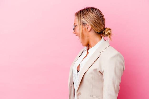Junge kaukasische gemischte rassengeschäftsfrau lokalisiert auf rosa hintergrund, die in richtung eines kopienraums schreit