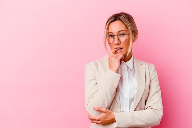 Junge kaukasische gemischte rassengeschäftsfrau lokalisiert auf rosa hintergrund entspanntes denken über etwas, das einen kopienraum betrachtet.