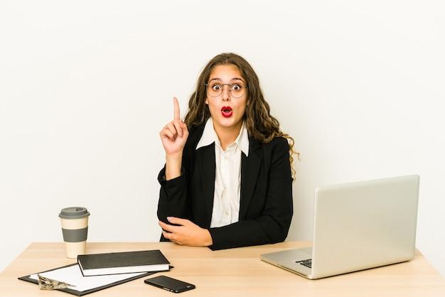 Junge kaukasische geschäftsfrau, die an ihrem desktop arbeitet, der einige große idee, konzept der kreativität hat.