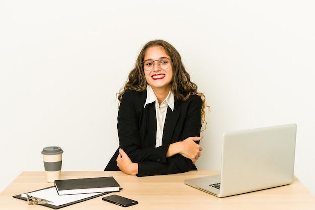 Junge kaukasische geschäftsfrau, die an ihrem desktop arbeitet, isoliert lächelnd.