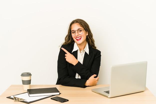 Junge kaukasische geschäftsfrau, die an ihrem desktop arbeitet, isoliert