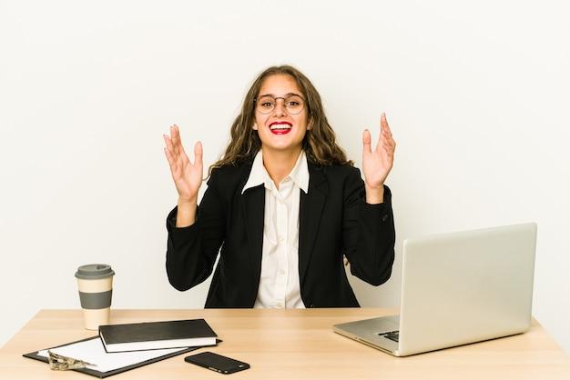 Junge kaukasische geschäftsfrau, die an ihrem desktop arbeitet, lokalisierte eine angenehme überraschung, aufgeregt und hob die hände.