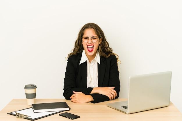 Junge kaukasische geschäftsfrau, die an ihrem desktop arbeitet, schreit sehr wütend und aggressiv schreiend.