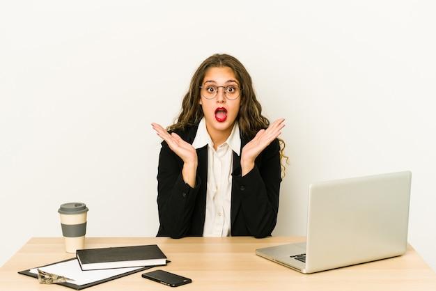 Junge kaukasische geschäftsfrau, die an ihrem desktop arbeitet, überrascht und schockiert.