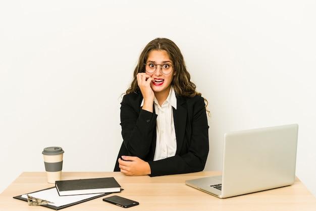 Junge kaukasische geschäftsfrau, die an ihren desktop beißenden fingernägeln arbeitet, nervös und sehr ängstlich.