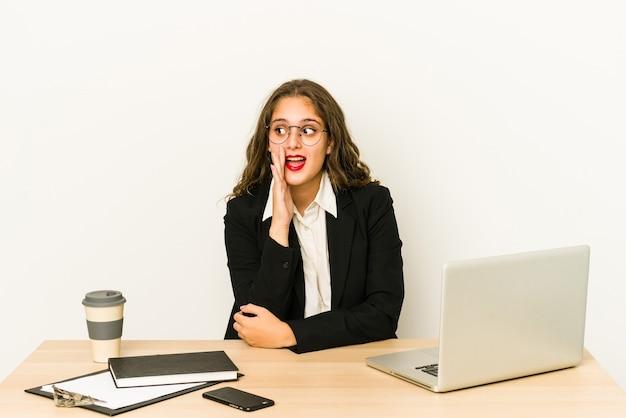 Junge kaukasische geschäftsfrau, die auf ihrem desktop arbeitet, isoliert